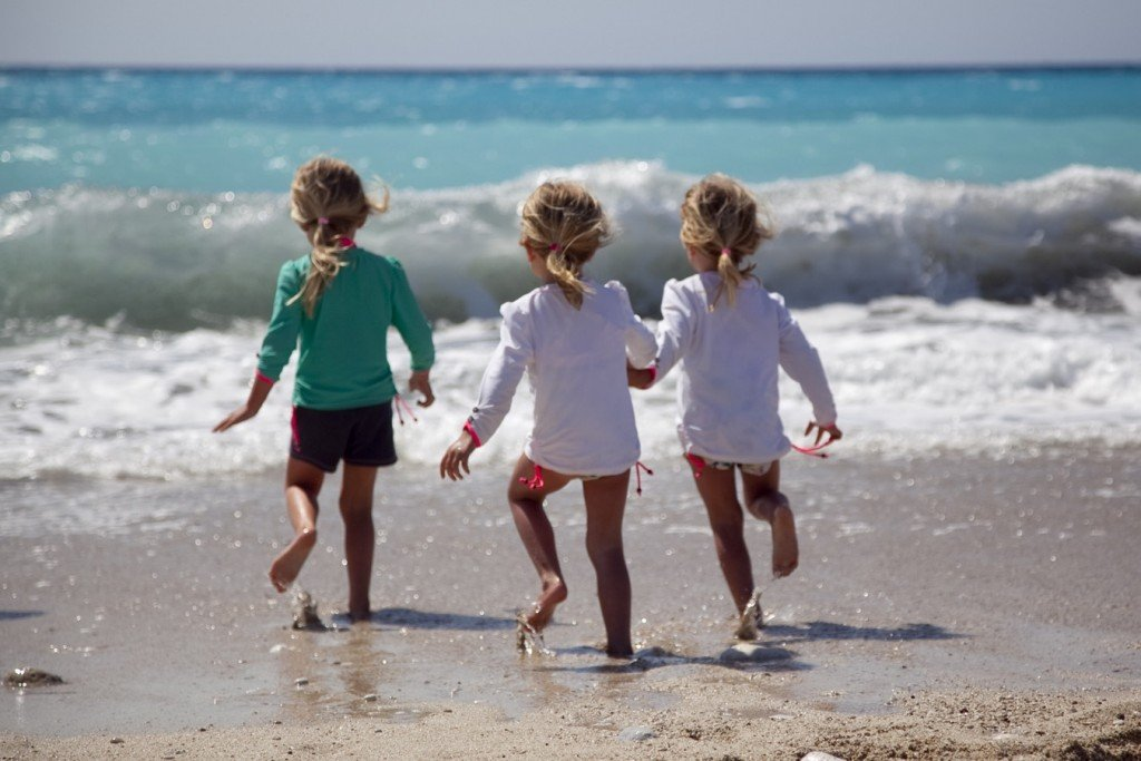Children playing on a beach in their swimming gear - one of the things you could pack in your beach ready beach bag
