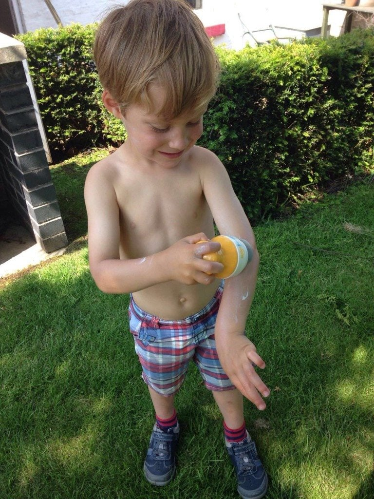 Child applying sunscreen independently using Solar Buddies