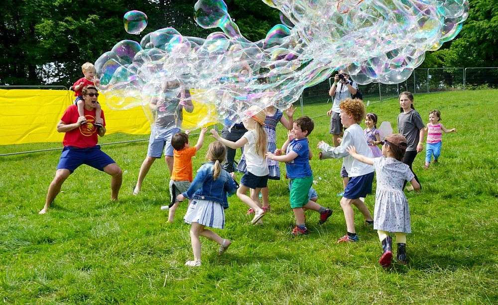 Elderflower Fields Festival - Families playing with giant bubbles. As featured in my Family Festivals for 2018 guide at www.minitravellers.co.uk