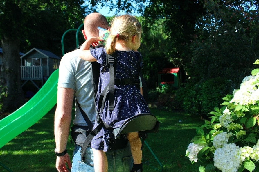 Carrying a child in the Freeloader Child Carrier, as part of a review on Mini Travellers