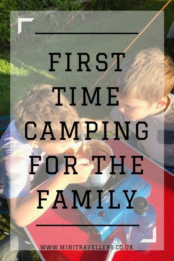 two boys cooking outside while camping with the words 'First Time Camping For The Family'