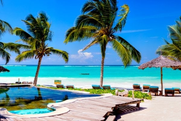 View of luxury hotel with palm trees, swimming pool and beach in Mexico.