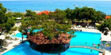 View of Luxury hotel with hut, swimming pool and beach in Turkey.