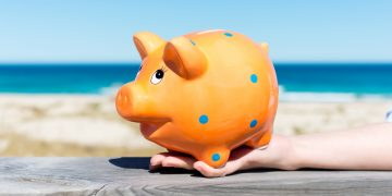 woman´s hand holding piggy bank by the beach